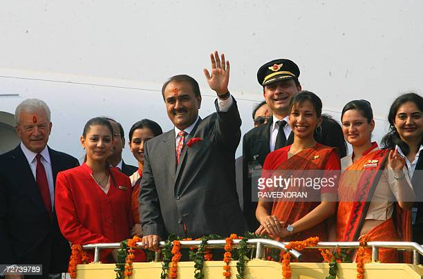 Union Minister of State for Civil Aviation Praful Patel waves as US Ambassador to India David Mullford and Air India hostesses with their new uniform...
