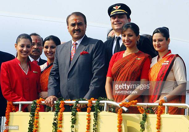Union Minister of State for Civil Aviation Praful Patel pauses with Air India air hostesses with their new uniform during the delivery of the Boeing...