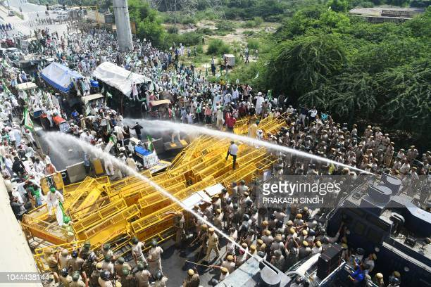 New Delhi police use water canons to disperse and stop farmer activists of the Bhartiya Kisan Union at the border with Ghazipur during their march to...