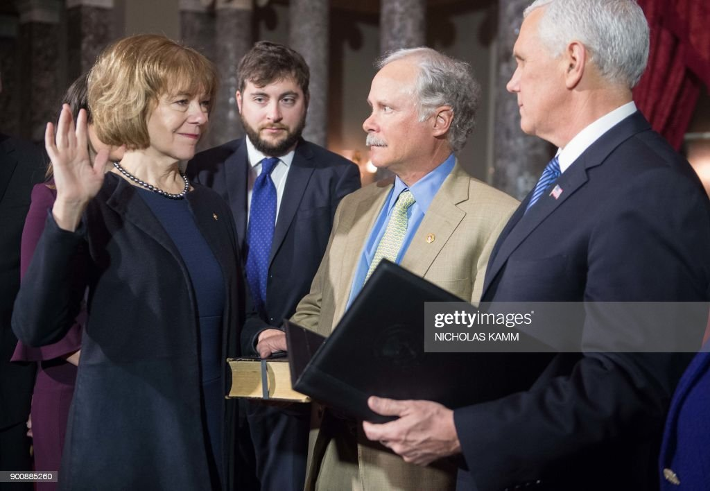 New Democratic US Senator from Minnesota Tina Smith (L) is ceremonially sworn in by Vice President Mike Pence (R) as her son Sam Smith (2nd ) and husband Archie Smith look on at the Capitol in Washington, DC, on January 3, 2018. /