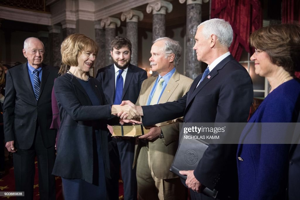New Democratic US Senator from Minnesota Tina Smith (2nd L) shakes hands with Vice President Mike Pence (R) at the Capitol in Washington, DC, on January 3, 2018 as her father F. Harlan Flint (L), son Sam Smith (3rd L), her husband Archie Smith and Democratic Senator from Minnesota Amy Klobuchar (R) look on. /