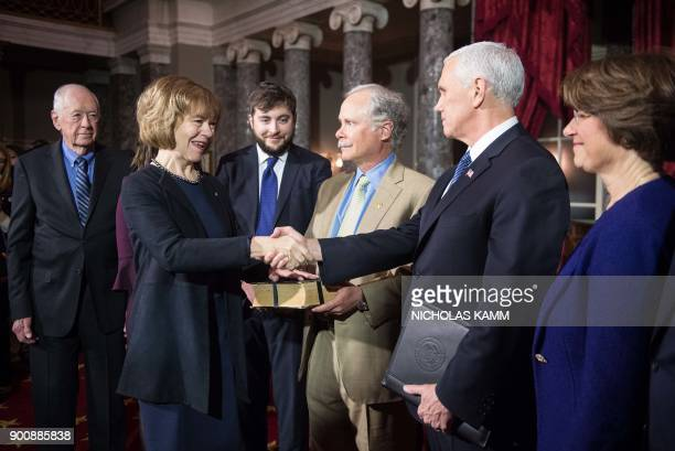 New Democratic US Senator from Minnesota Tina Smith shakes hands with Vice President Mike Pence at the Capitol in Washington DC on January 3 2018 as...