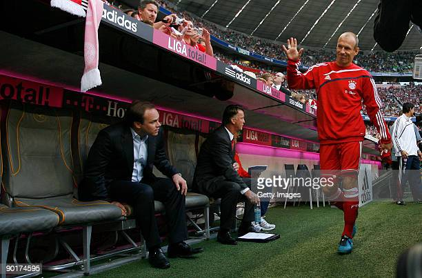 New Dutch forward Arjen Robben of Bayern waves to supporters as he walks past head coach Louis van Gaal and manager Christian Nerlinger before the...