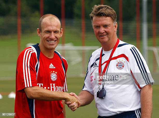 New Dutch forward Arjen Robben of FC Bayern Muenchen and FC Bayern Muenchen head coach Louis van Gaal shake hands during the Bayern Muenchen training...