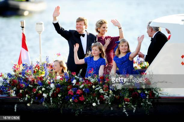 New Dutch King WillemAlexander and Queen Maxima with Crown Princess Amalia Princess Alexia and Princess Ariane wave to spectators and performers on...