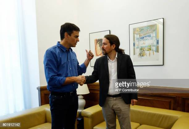 New elected leader of Spanish Socialist Party Pedro Sanchez and leader of left wing party Podemos Pablo Iglesias shake hands as they pose before a...