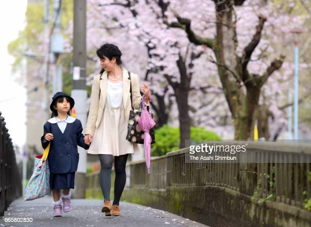 A new elementary school pupil walks with her mother next to bloomed cherry blossom to attend the welcome ceremony on April 7 2017 in Osaka Japan