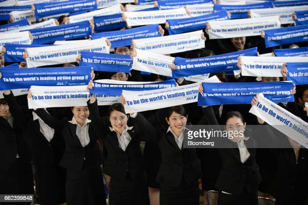 New employees of ANA Group including All Nippon Airways Co hold banners as they pose for photographs during an initiation ceremony at the company's...