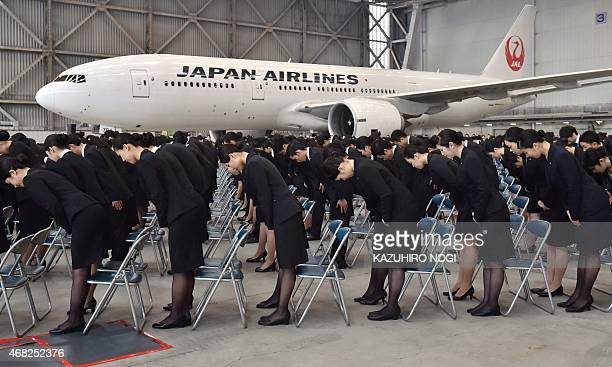 New employees of Japan Airlines Group bow their heads during their entrance ceremony at a hangar with a Boeing 777 in Tokyo on April 1 2015 Thirty...