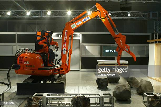 New Energy and Industrial Technology Development Organization's HRP2 robot operates a machine at Robodex2003 April 2 2003 in Yokohama Japan HRP2 goes...