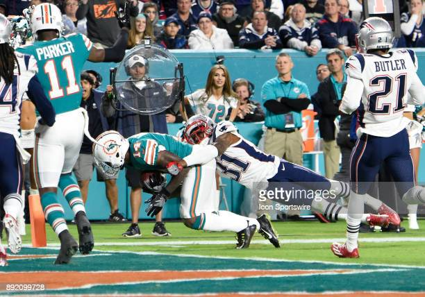 New England defensive back Jonathan Jones tackles Miami Dolphins wide receiver Jarvis Landry as he scores during an NFL football game between the New...