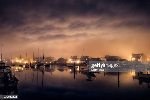 new england lagoon with docked boats on a foggy night - eastern usa stock photos and pictures