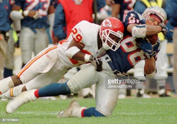 New England Patriot Terry Glen is brought down by as Kansas City Chief Mark McMillan in the third quarter of action 11 October at Foxboro Stadium in...