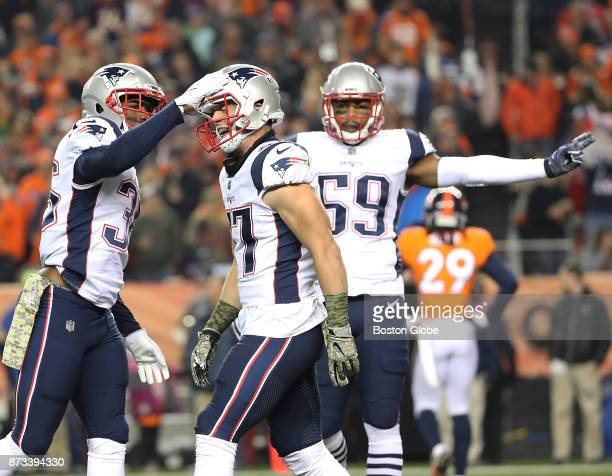 New England Patriots Brandon King slaps teammate Jaobb Hollister on the helmet after he recovered a fumble against the Denver Broncos during first...