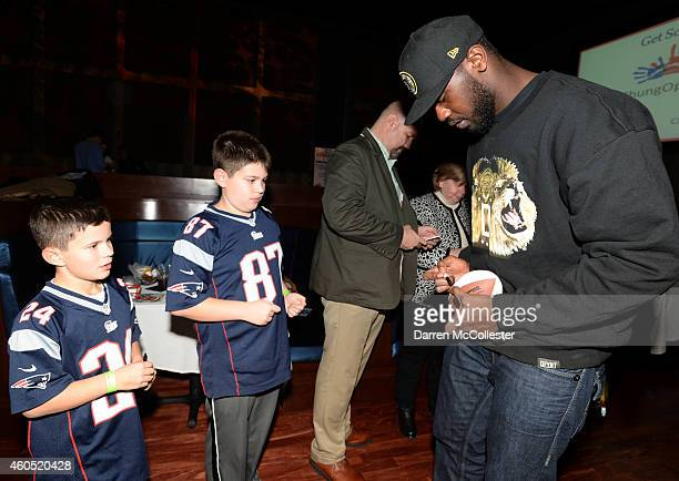 New England Patriots Chandler Jones signs autographs for Matthew and Nathan during Patrick Chung's Open Mic Holiday Party benefiting Boston...