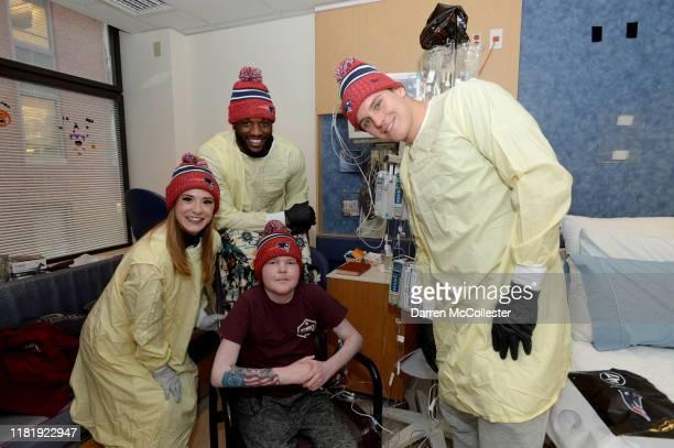 New England Patriots cheerleader Alexis Melvin, Shilique Calhoun, and Ryan Izzo visit with CJ at Boston Children's Hospital November 12, 2019 in...