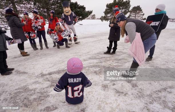 New England Patriots cheerleader Michaela Main shakes pom poms getting the attention of 15monthold Makenna King who is wearing a Tom Brady jersey at...