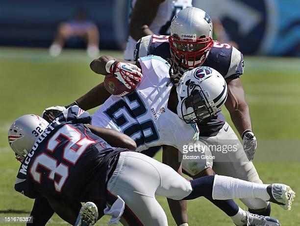 New England Patriots cornerback Devin McCourty and New England Patriots linebacker Jerod Mayo bring down Tennessee Titans running back Chris Johnson...