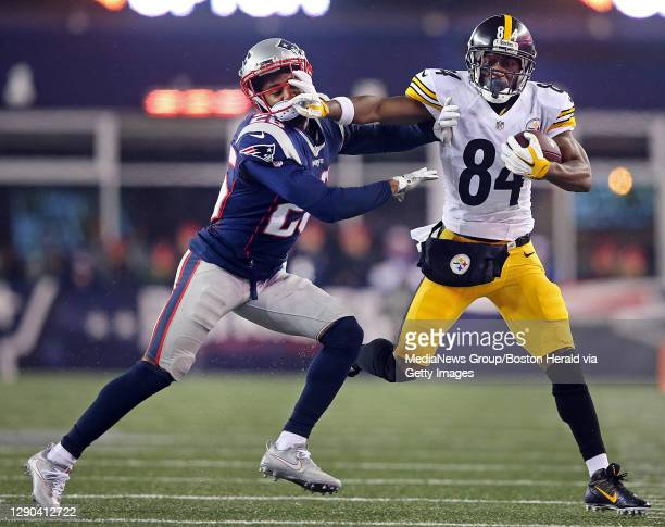 New England Patriots cornerback Logan Ryan gets a stiff arm to the face from Pittsburgh Steelers wide receiver Antonio Brown during the second...