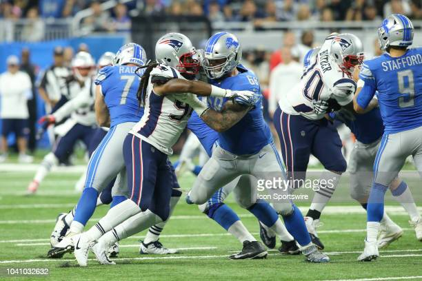 New England Patriots defensive end Adrian Clayborn fights through a block by Detroit Lions tackle Taylor Decker during a regular season game between...