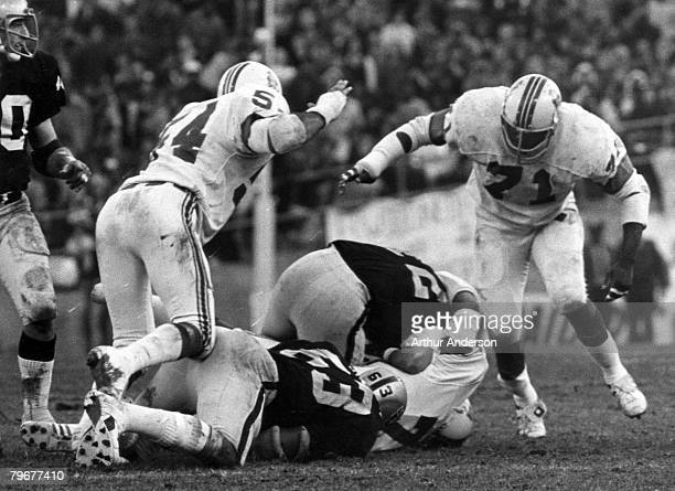 New England Patriots defensive end Mel Lunsford sacks Oakland Raiders quarterback Ken Stabler with Patriots linebacker Steve Zobel and defensive...