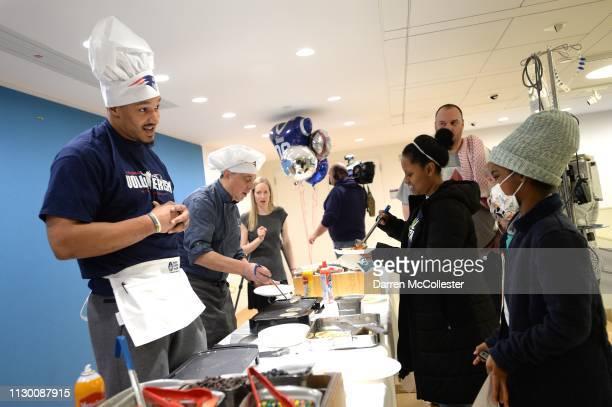 New England Patriot's Derek Rivers flips pancakes for Asada at Boston Children's Hospital March 12 2019 in Boston Massachusetts