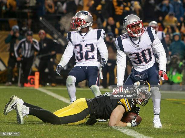 New England Patriots Devin McCourty and Duron Harmon look for a call after Pittsburgh Steelers tight end Jesse James, left, lunged over the goal line...