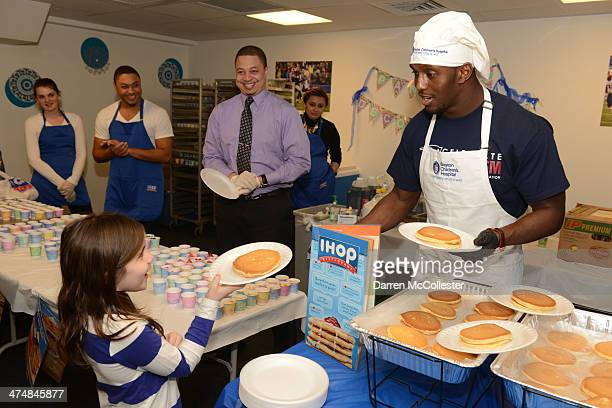 New England Patriots' Devin McCourty serves pancakes to Rhianna at Boston Children's Hospital on February 25 2014 in Boston Massachusetts