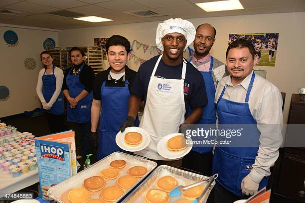 New England Patriots' Devin McCourty serves up pancakes with the IHOP volunteers at Boston Children's Hospital on February 25 2014 in Boston...