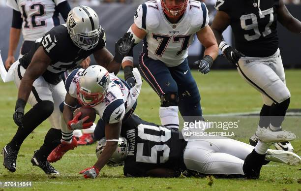 New England Patriots' Dione Lewis is tackled by Oakland Raiders' Bruce Irvin and Nicholas Morrow during the 2016 NFL week 11 regular season football...