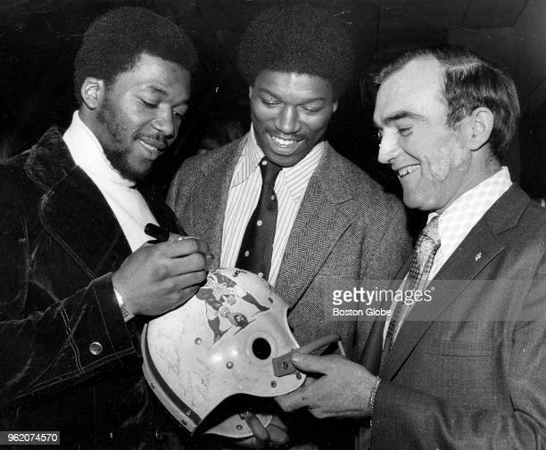 New England Patriots draft choices Darryl Stingley, left, and Sam Cunningham, center, sign Mike Conners autograph helmet at the Sidney Hill Country...