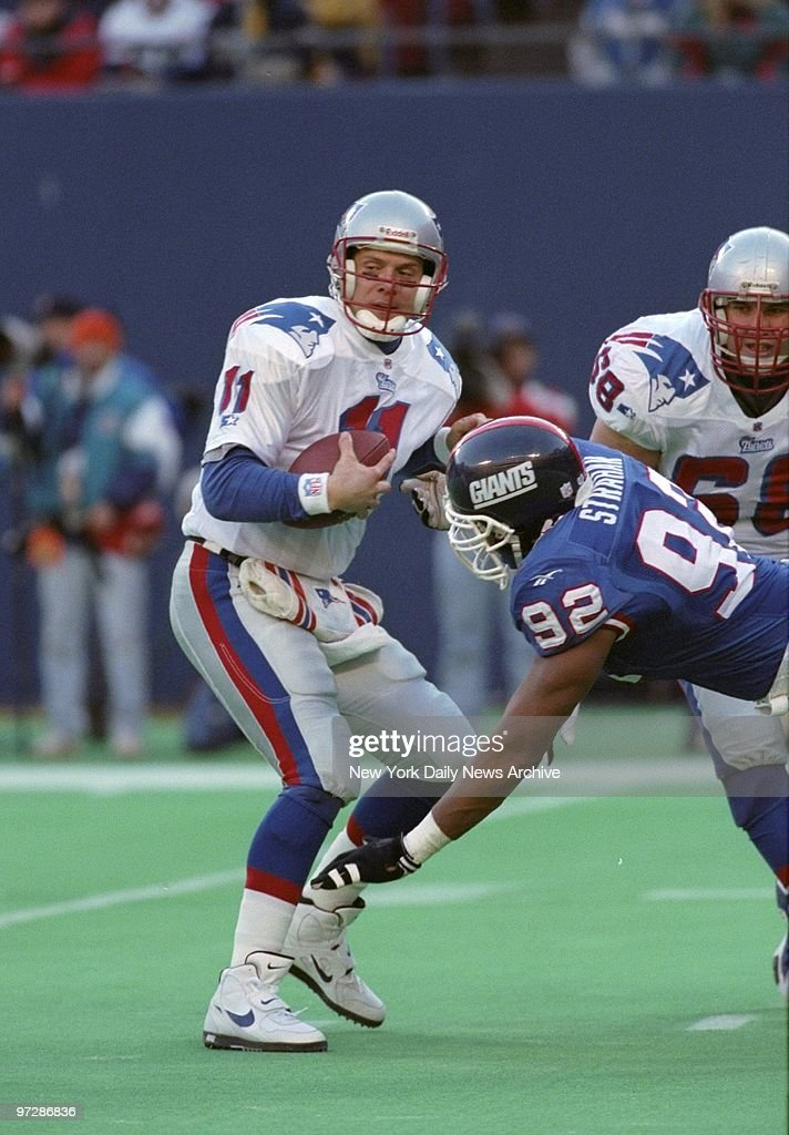 New England Patriots' Drew Bledsoe is rushed by Michael Stra : News Photo