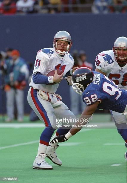 New England Patriots' Drew Bledsoe is rushed by Michael Strahan in the third quarter during game vs New York Giants at Giants Stadium