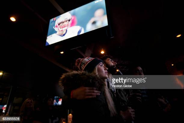 New England Patriots fans April Saenz and Viral Singh stand under a screen displaying New England Patriots quarterback Tom Brady as they watch the...