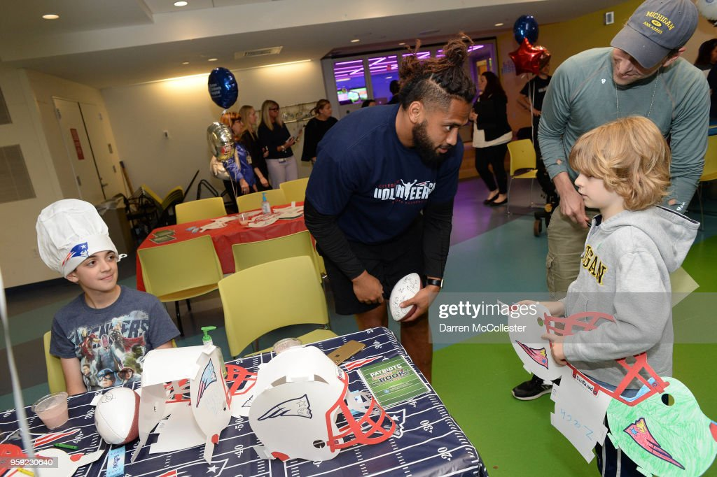 New England Patriots Harvey Langi visits with Evan (L) and Zachary at Boston Children's Hospital on May 16, 2018 in Boston, Massachusetts.