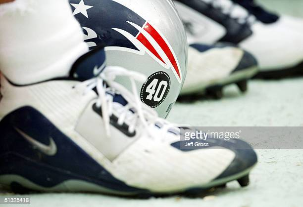 New England Patriots helmet bearing a decal with the number 40 of the late Pat Tillman rests between a players shoes during a game against the...
