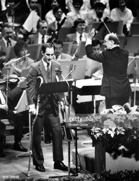 New England Patriots injured quarterback Steve Grogan stands on crutches as he reads 'Twas the Night Before Xmas' as Boston Pops conductor John...