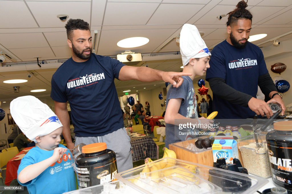 New England Patriots Kyle Van Noy (L) and Harvey Langi make smoothies with Daniel and Evan at Boston Children's Hospital on May 16, 2018 in Boston, Massachusetts.