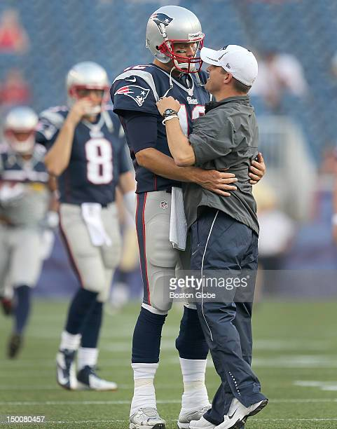 New England Patriots offensive coordinator Josh McDaniels and New England Patriots quarterback Tom Brady share an embrace as the team took to the...