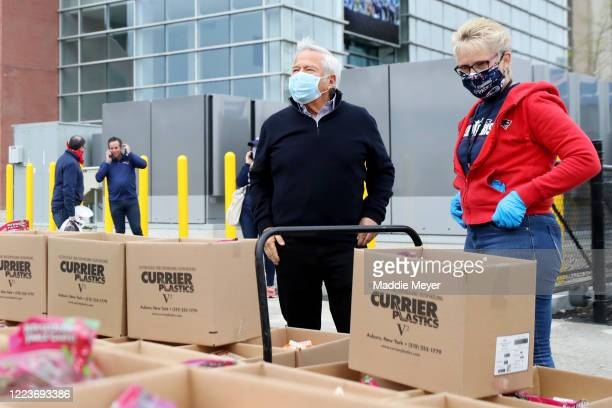 New England Patriots owner Robert Kraft and Patriots Community Relations Director Donna Spigarolo look over boxes of food at the SoupR Bowl at...