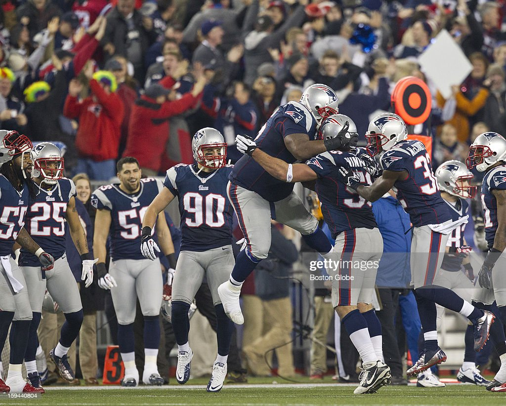 New England Patriots player Vince Wilfork, left, and Aqib Talib, right, jump on teammate Rob Ninkovich after his interception against the Houston Texans during third quarter action as the New England Patriots hosted the Houston Texans in an NFL AFC Divisional Playoff Game at Gillette Stadium, Jan. 13, 2013.