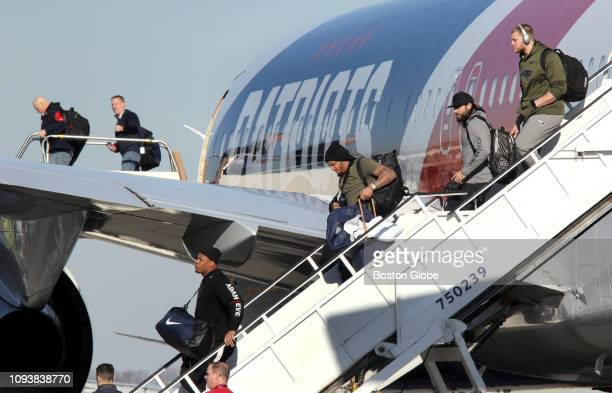 New England Patriots players including the injured Patrick Chung center depart from the Patriots plane as the team arrives at TF Green Airport in...