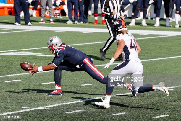 New England Patriots quarterback Cam Newton grabs a bad snap as Denver Broncos linebacker Derrek Tuszka chases during a game between the New England...
