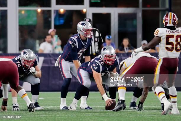 New England Patriots quarterback Danny Etling calls signals over New England Patriots offensive lineman Luke Bowanko during a preseason NFL game...