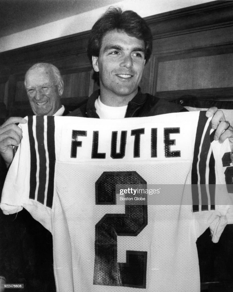 New England Patriots quarterback Doug Flutie displays his new number as Patriots owner Billy Sullivan, left, looks on during a press conference announcing his signing with the team in Foxborough, Mass., Oct. 13, 1987.