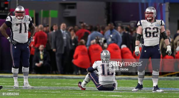 New England Patriots quarterback Tom Brady and offensive linemen Cameron Fleming and Joe Thuney are pictured following the strip sack in the fourth...