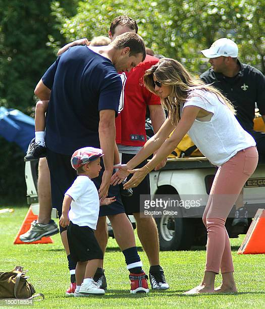 New England Patriots quarterback Tom Brady carries his son John as he chatted with Saints quarterback Drew Brees at the end of practice as Brady's...
