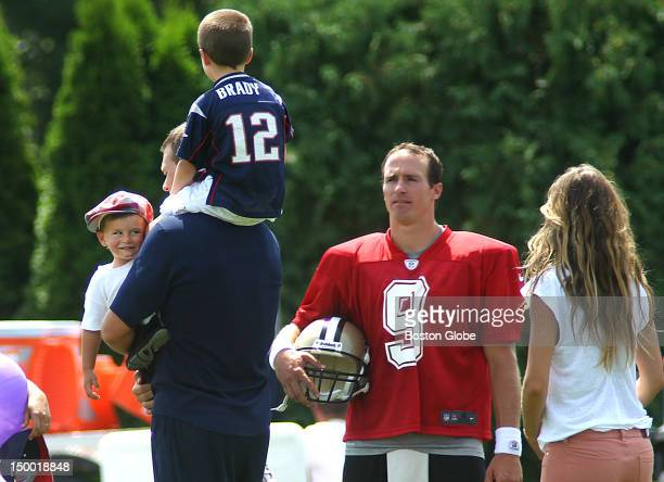 New England Patriots quarterback Tom Brady carries his sons Benjamin left and John as he chatted with Saints quarterback Drew Brees with Brady's wife...