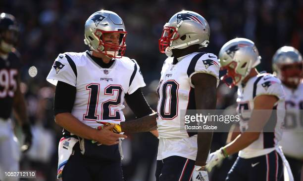 New England Patriots quarterback Tom Brady congratulates New England Patriots wide receiver Josh Gordon on his catch and run for extra yardage during...