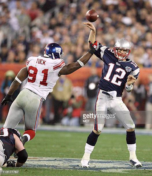 New England Patriots' quarterback Tom Brady gets a pass away under the pressure of the New York Giants' Justin Tuck in the second half of Super Bowl...